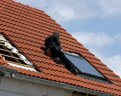 image of working putting solar panel on house